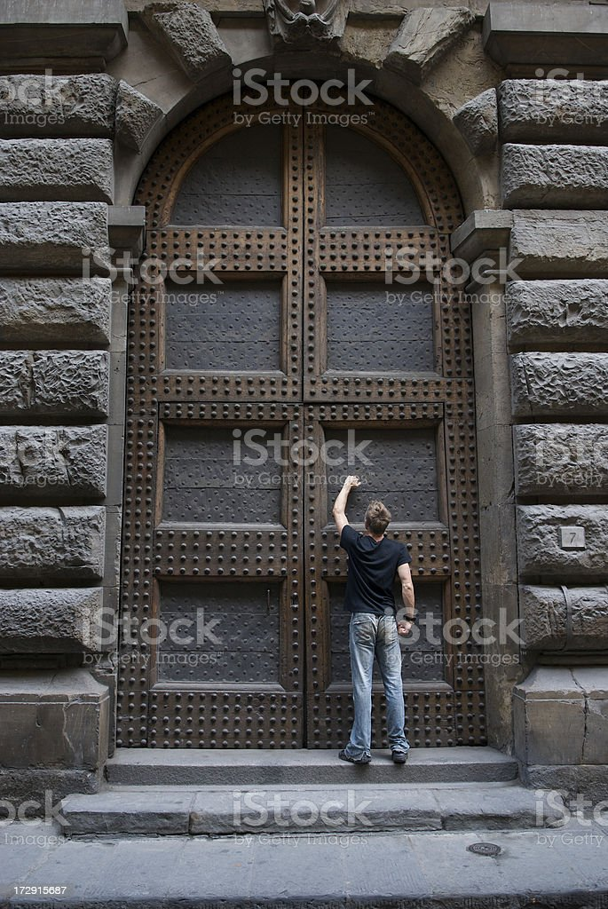 Knock-Knock! Small Man Knocking on Big Door stock photo
