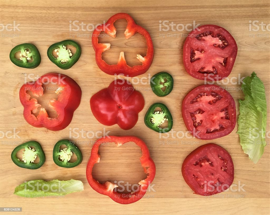 Knolling sliced vegetables on wood cutting board stock photo