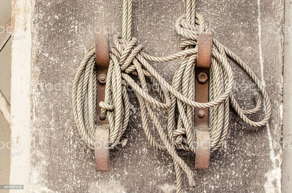 Knot rope tied around stake on cement wall stock photo