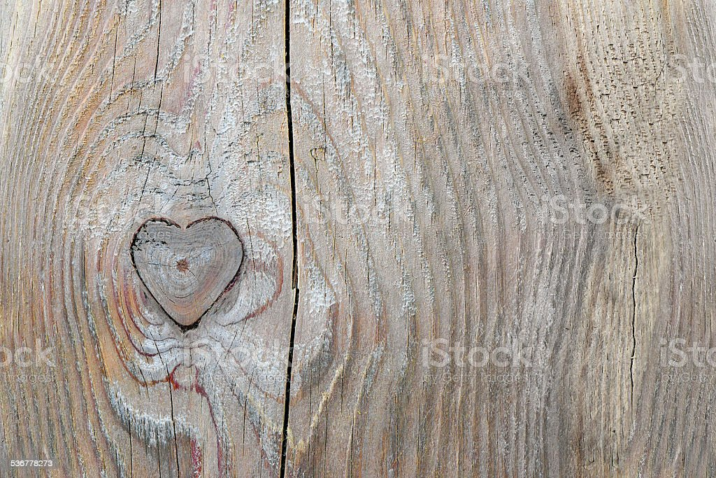 knothole in heart shape in old wood, love background stock photo