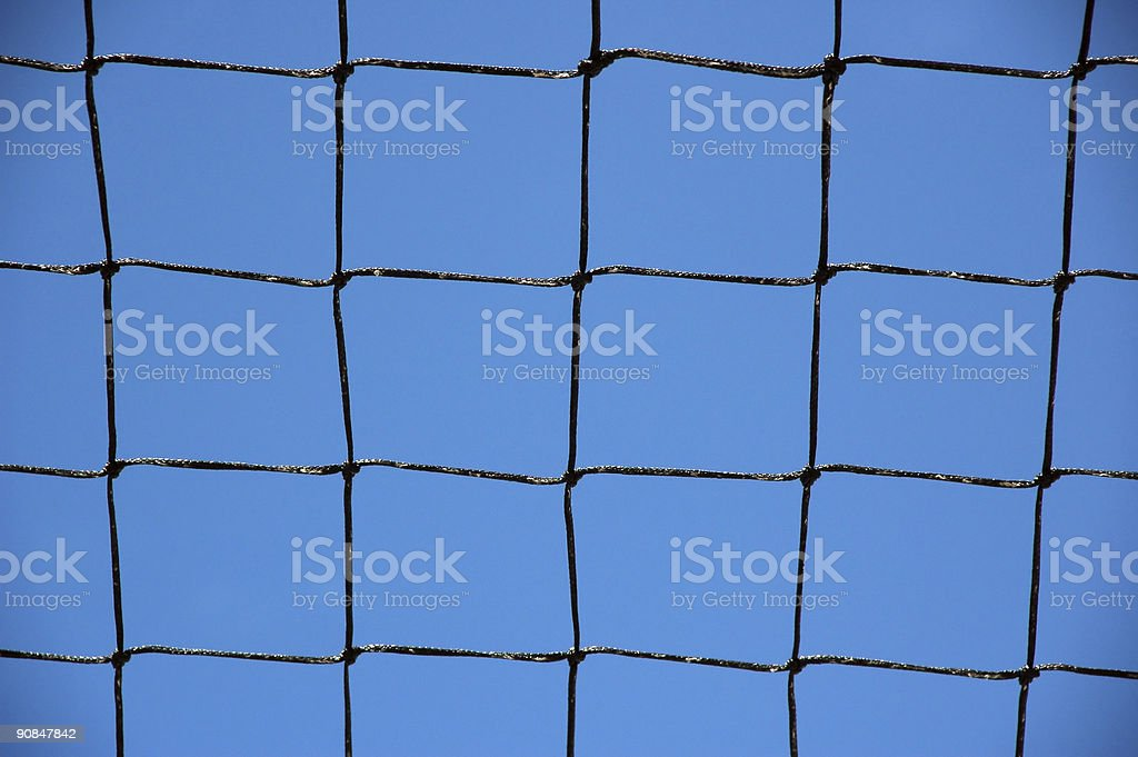 Knotted grid like a chain-link fence against cloudless blue sky stock photo
