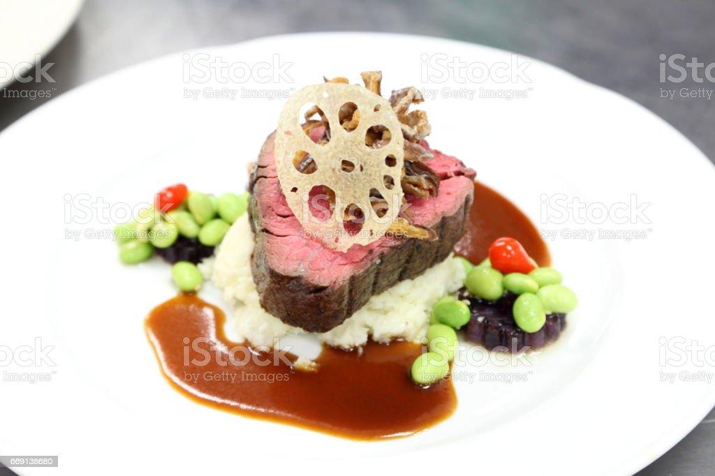 Kobe beef tenderloin, wasabi mashed potato, edamame sauce, lotus root chip. stock photo