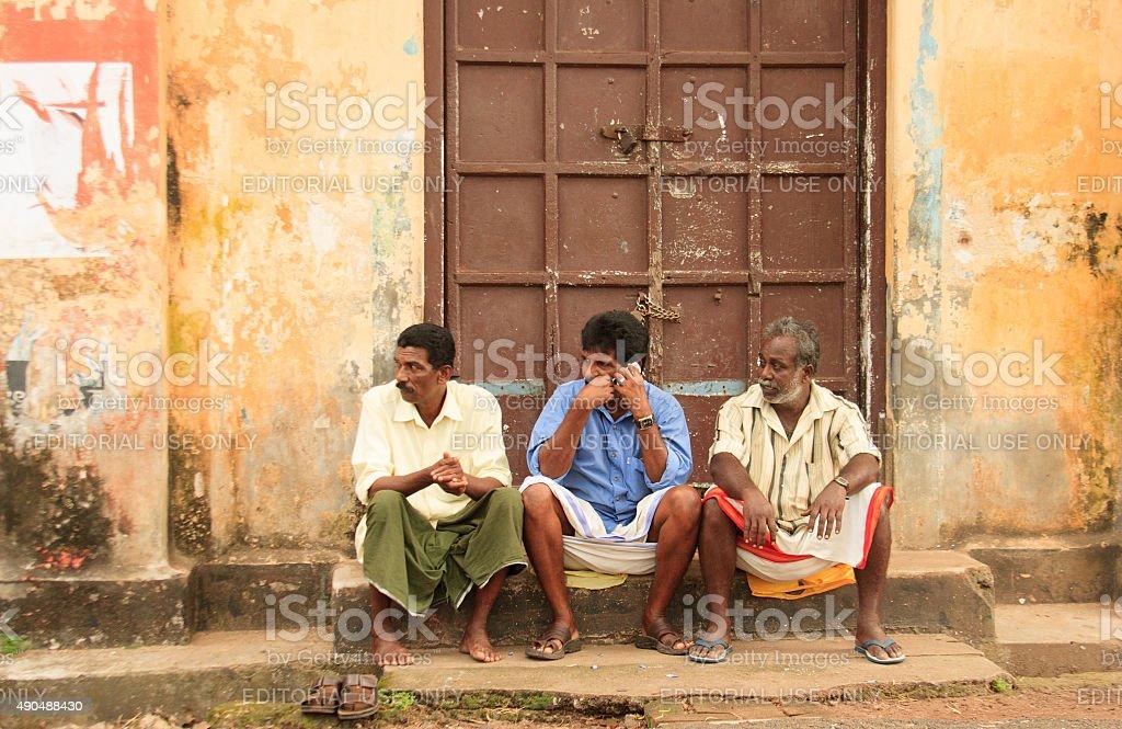 Kochi (Kerala), India: Men Sitting on Colorful Wall, Old Town stock photo