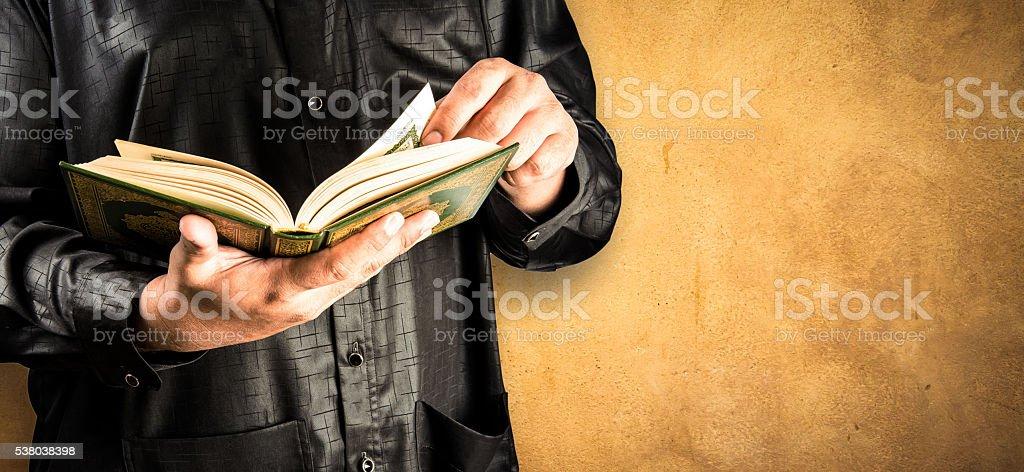 Koran in hand stock photo