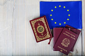 Koran,EU flag and passports on a wooden surface.