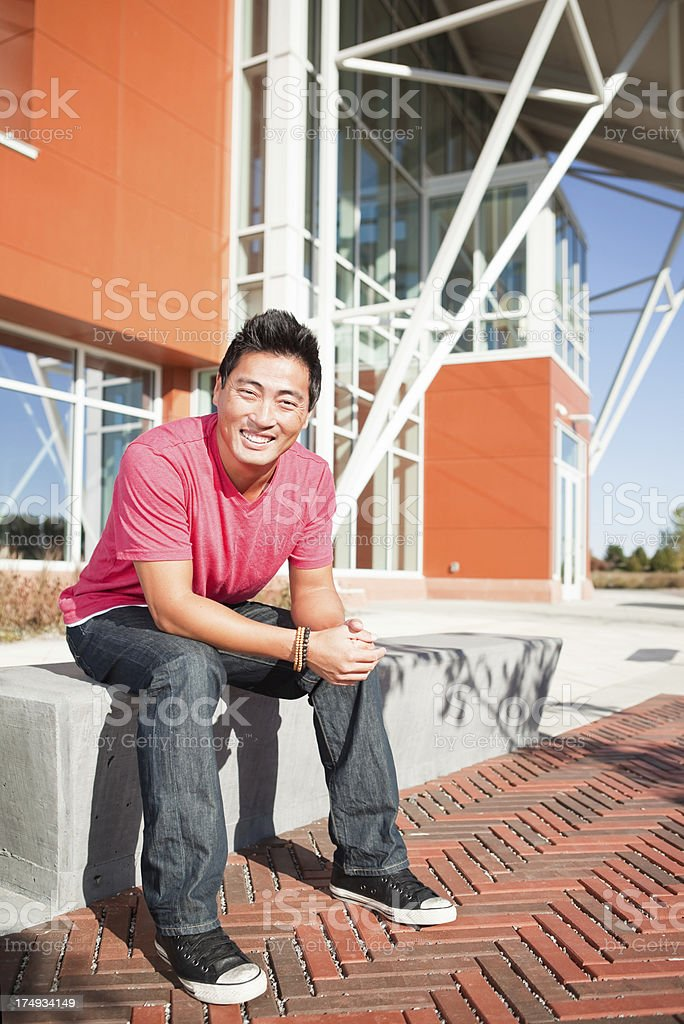 Korean Man Sitting on Concrete Bench Outdoors royalty-free stock photo