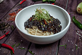 Korean noodle with black sauce in white bowl on wooden