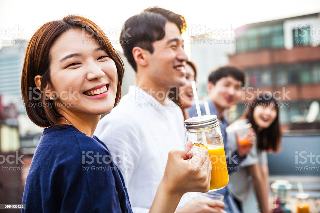 Korean woman with friends during a rooftop party in Seoul stock photo