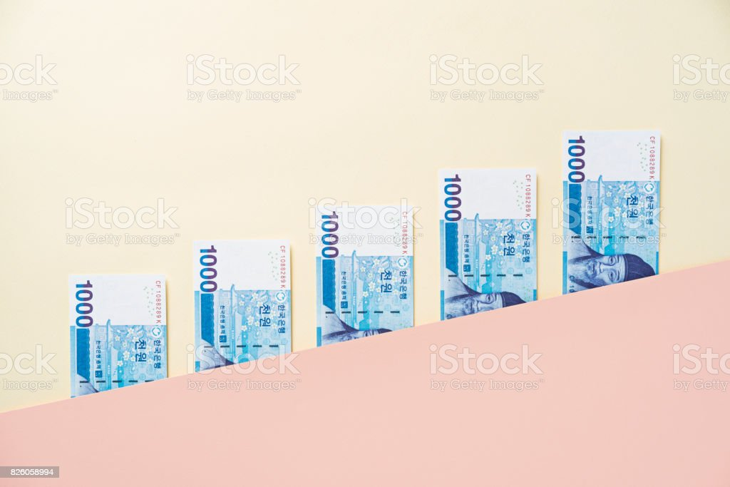 Korean won banknotes between diagonal pink yellow color block layers stock photo