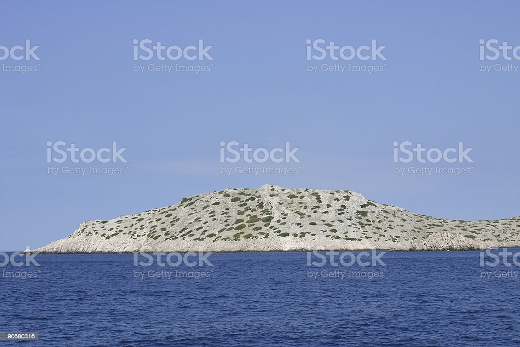 Kornati - Bare greyish islet on azure royalty-free stock photo