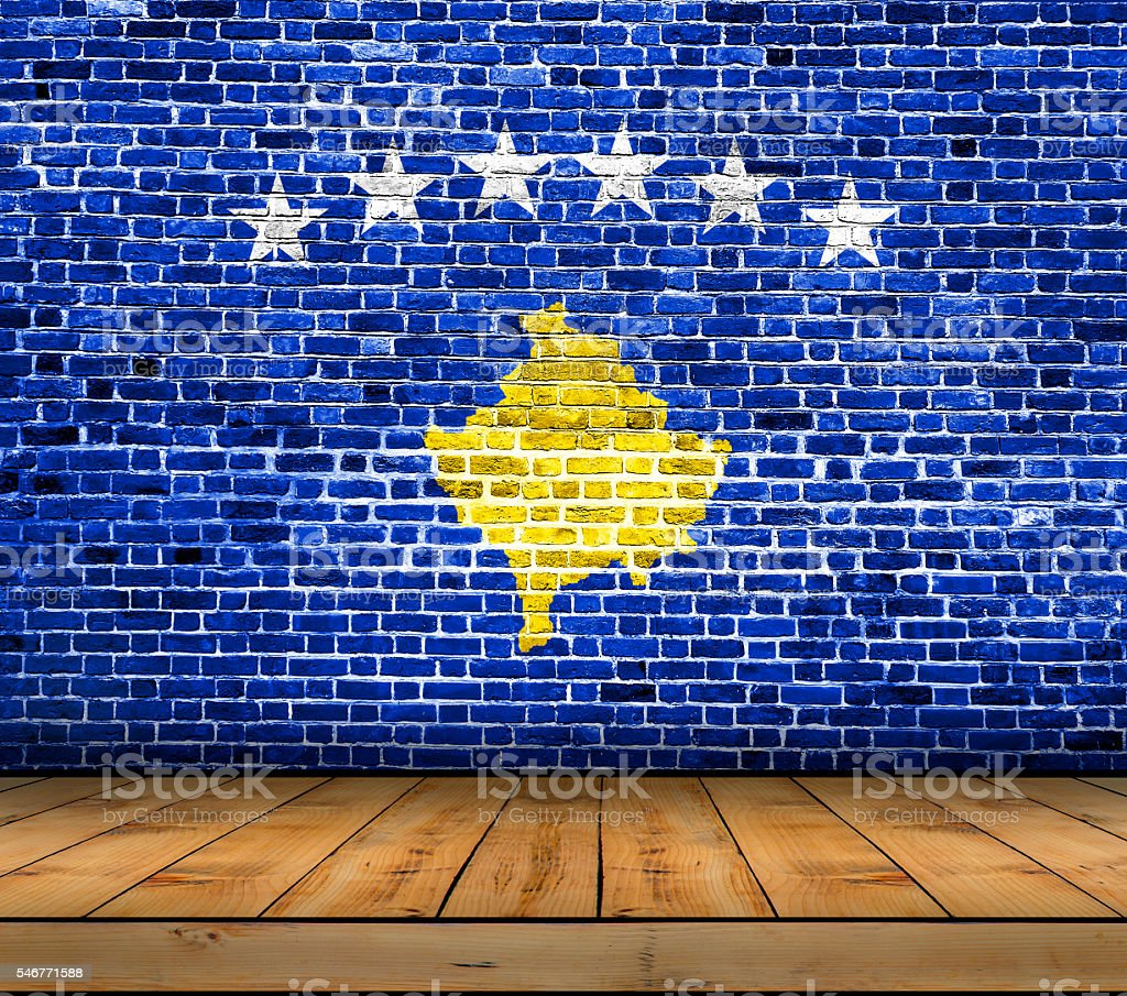 Kosovo flag painted on brick wall with wooden floor stock photo