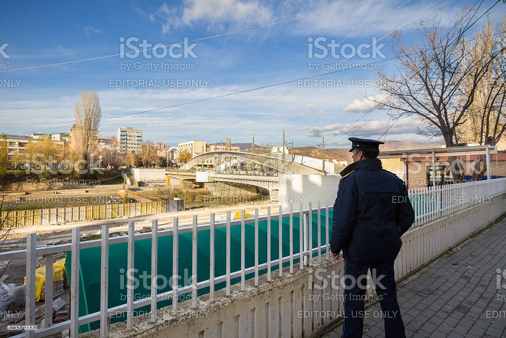 Kosovo Policeman watching the bridge over the Ibar river stock photo