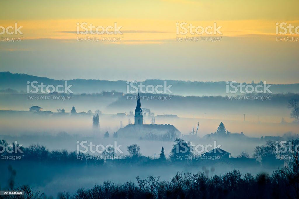 Krizevci cathedral in fog landscape stock photo