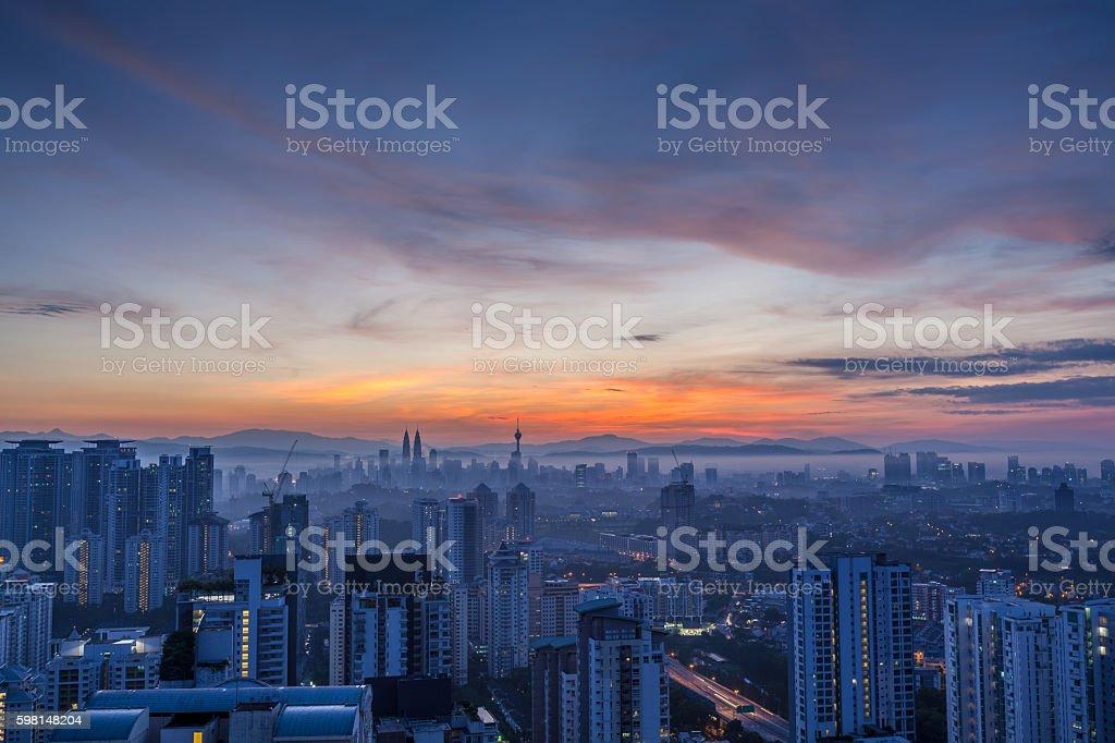 Kuala Lumpur cityscape at dawn with cloudy orange sky, wide stock photo