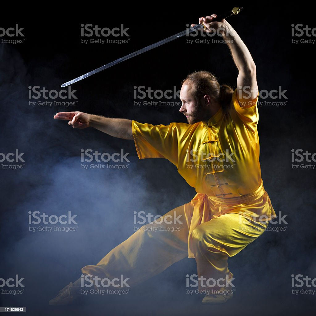 Kung fu fighting position with Jian sword on dark background royalty-free stock photo