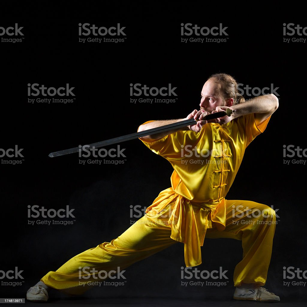 Kung fu fighting position with Jian sword on dark background stock photo