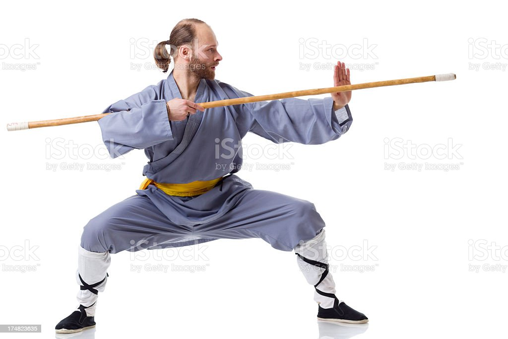 Kung Fu fighting position with Wushu Cudgel isolated on white stock photo