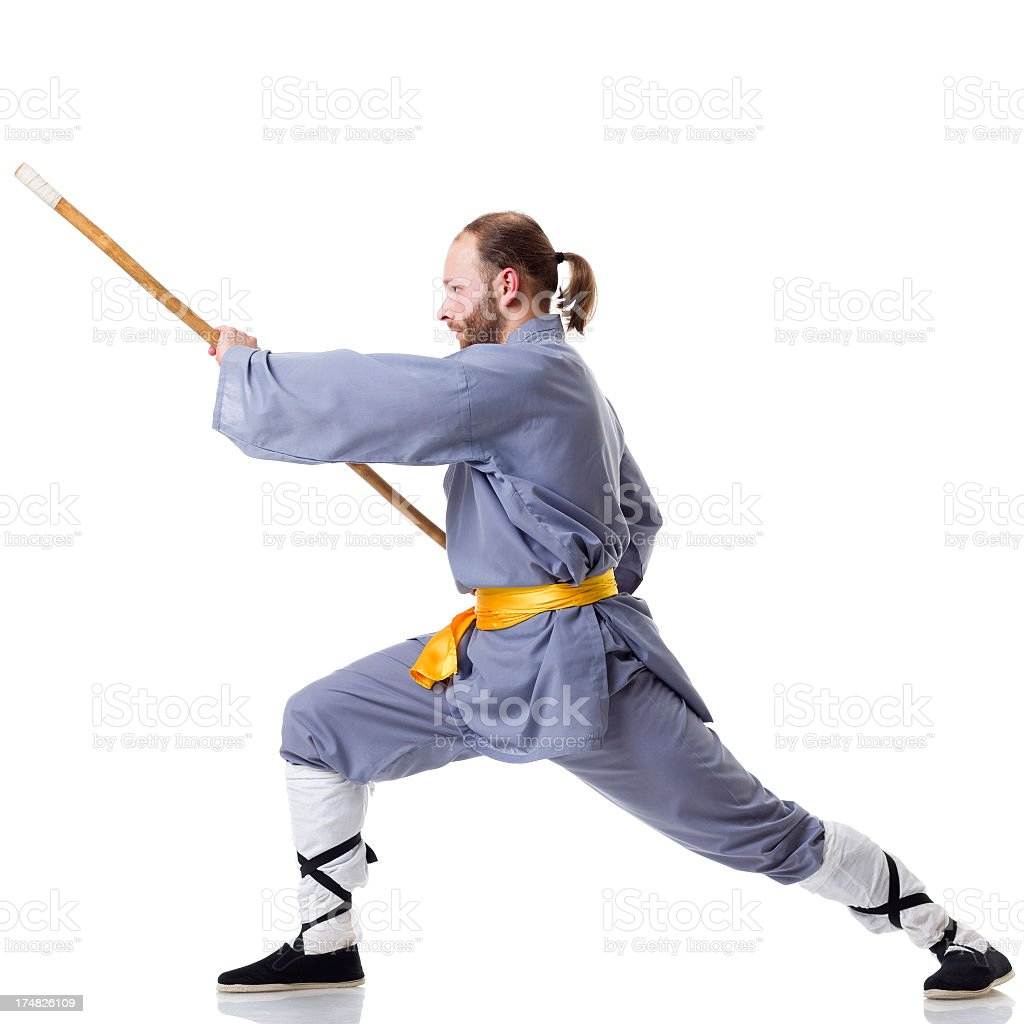 Kung Fu fighting position with Wushu Cudgel isolated on white royalty-free stock photo