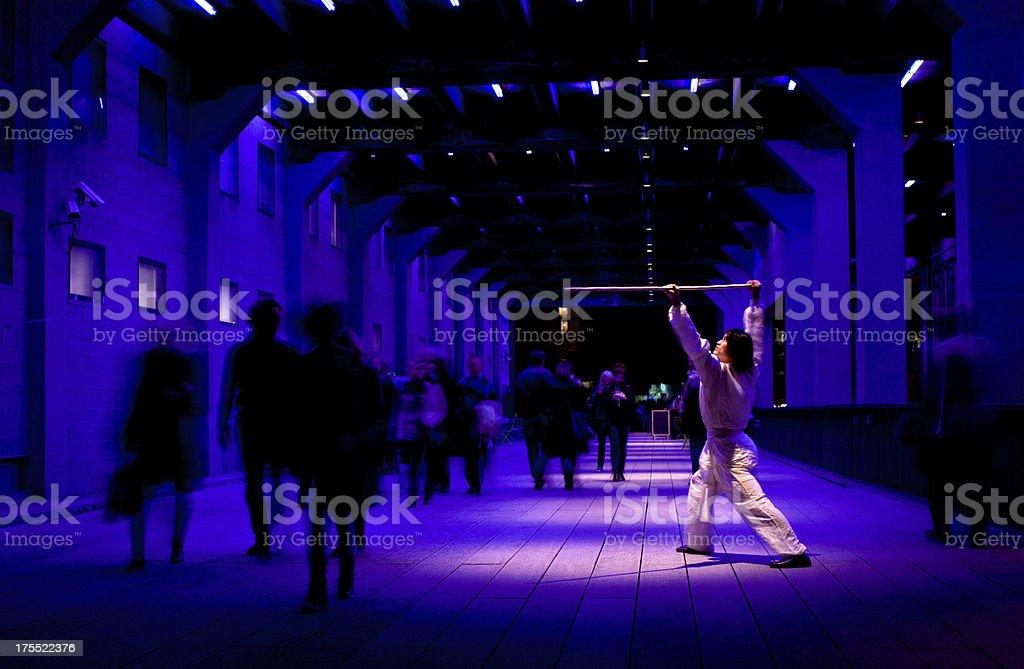 Kung fu warrior training at night as people walk past royalty-free stock photo