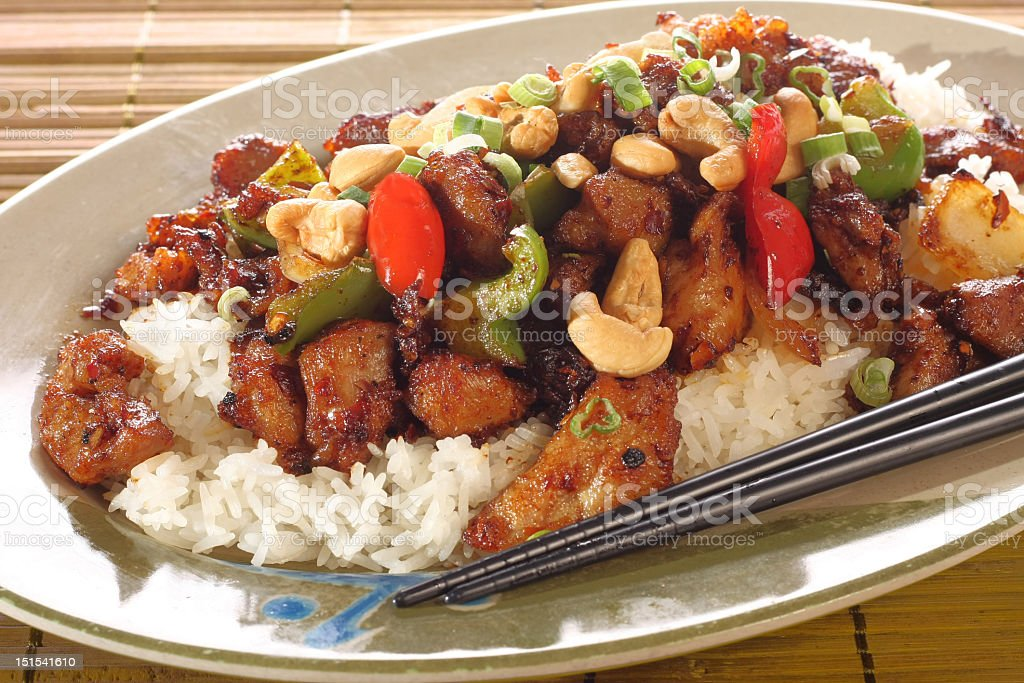 Kung pao chicken and rice on plate with chopsticks royalty-free stock photo