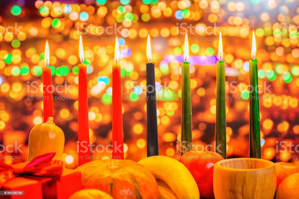 Kwanzaa celebration concept with seven candles red, black and green, gift box, pumpkin, bowl and fruit on light blur bokeh background, close up stock photo