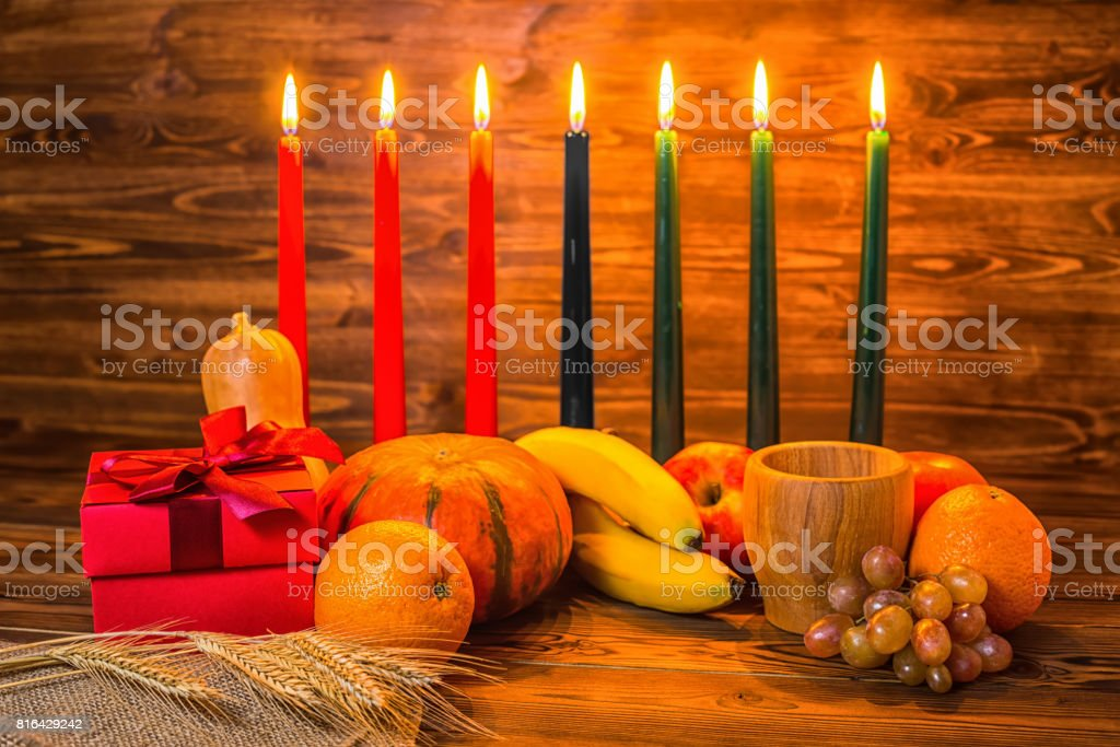 Kwanzaa holiday concept with traditional lit candles, gift box, pumpkins, ears of wheat, grapes, orange, banana, bowl and fruits on wood background stock photo