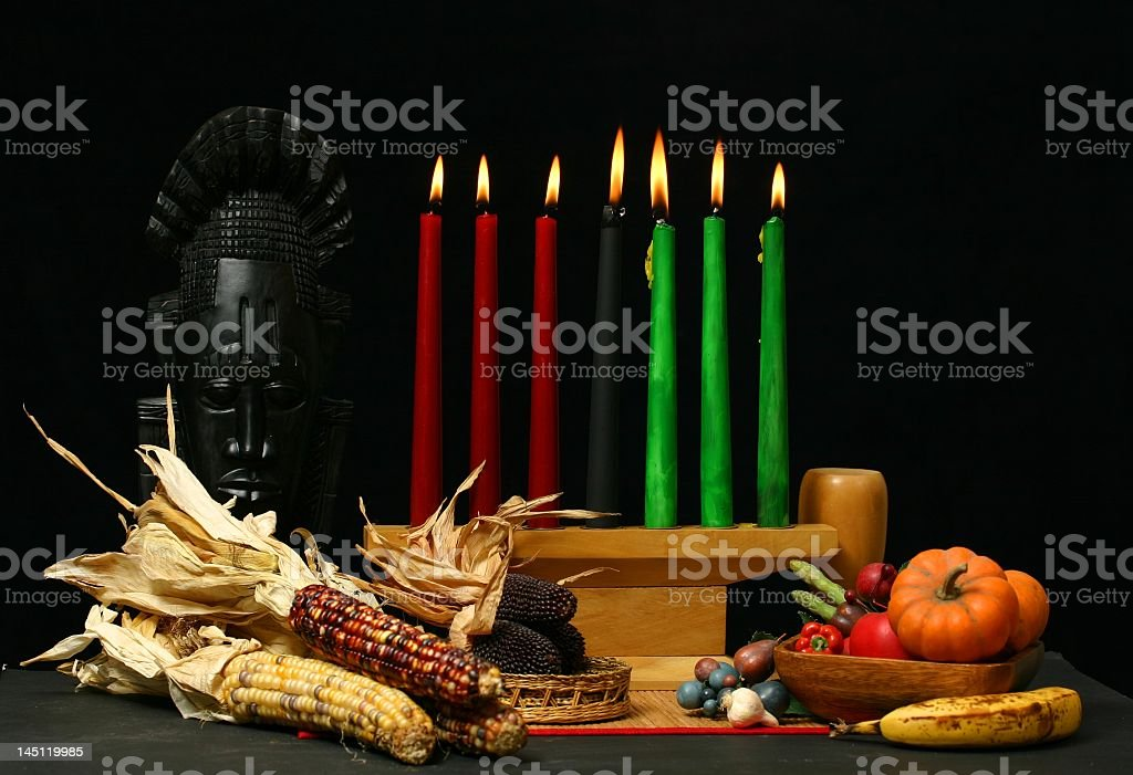 Kwanzaa table setting with candle and dried corn cobs stock photo