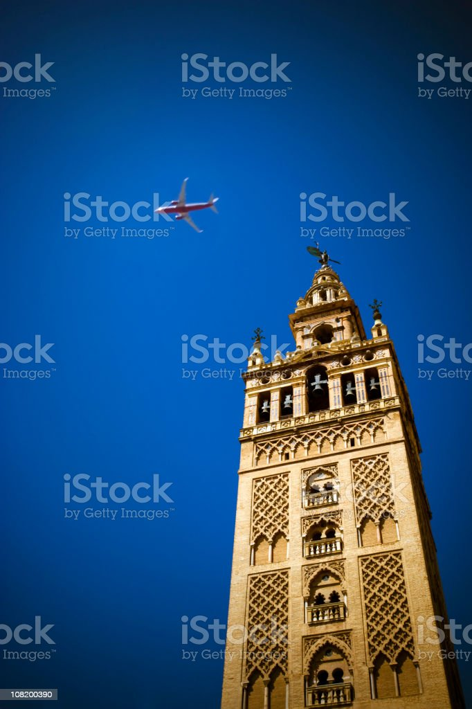 La Giralda Cathedral Bell Tower with Airplane in Sky royalty-free stock photo
