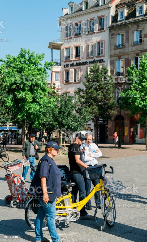La Poste manger interviewed in city center during exposition of green postal vans stock photo