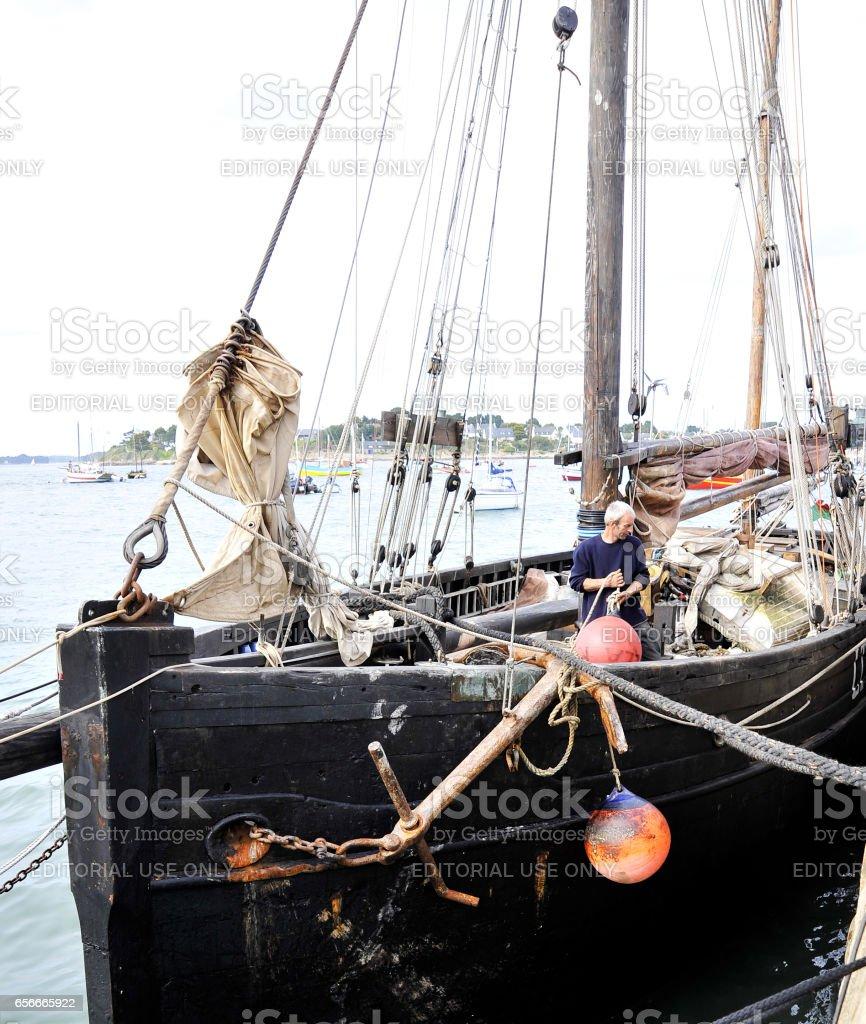La Semaine du Golfe; bi-annual classic boat festival. A classic fishing boat in harbor, crewman on deck. stock photo
