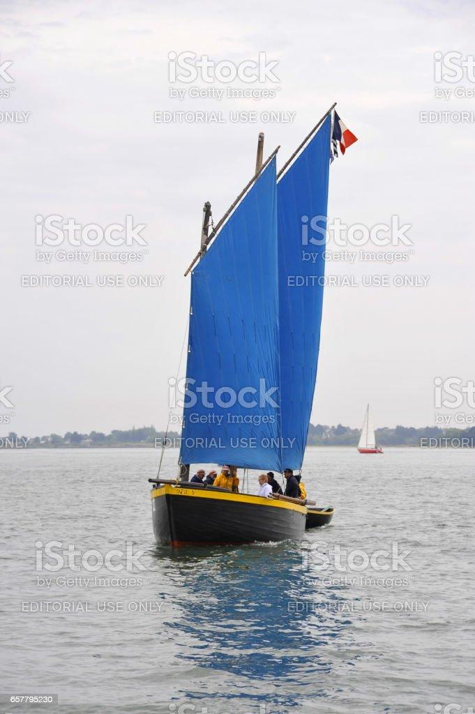 La Semaine du Golfe; bi-annual classic boat festival. A classic fishing boat with blue sails. stock photo