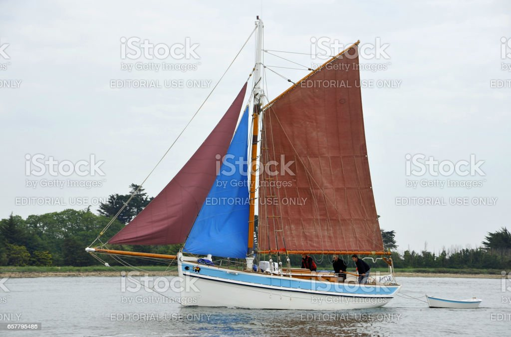 La Semaine du Golfe; bi-annual classic boat festival. A classic fishing boat with blue and red sails. stock photo