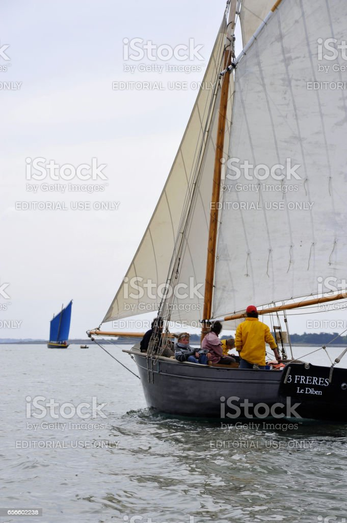 La Semaine du Golfe; bi-annual classic boat festival. A classic little dinghy; 3 Freres (3 brothers), overtakes us. stock photo