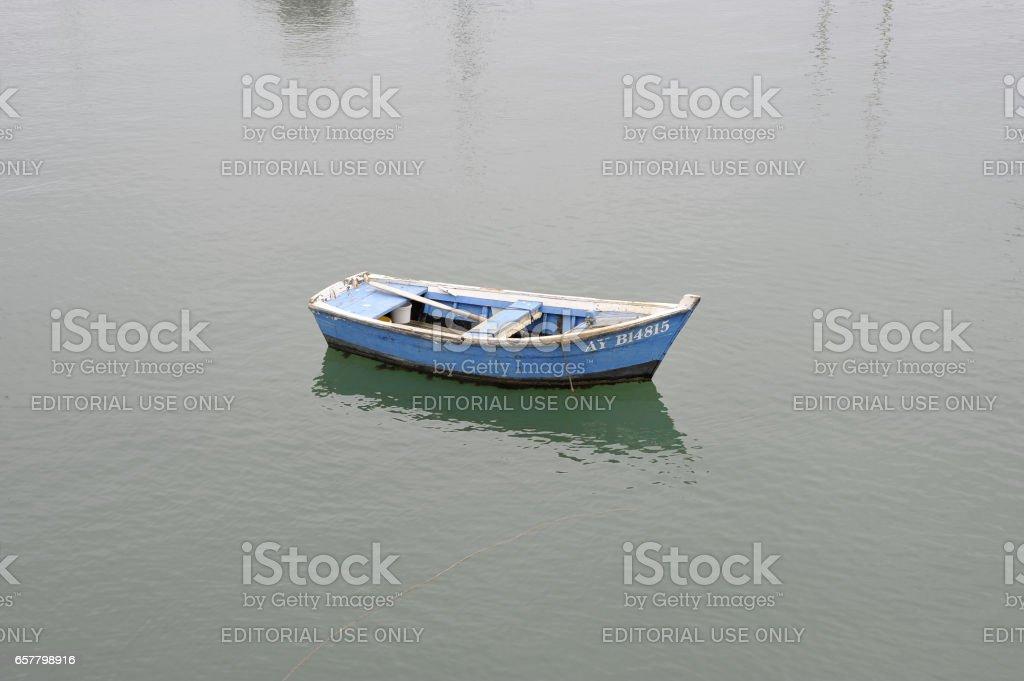 La Semaine du Golfe; bi-annual classic boat festival. All alone, a light-blue rowing boat waits on a clam sea. stock photo