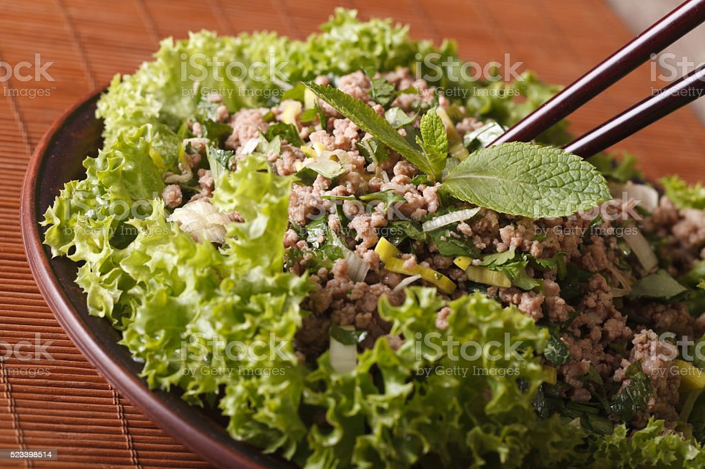 Laab Thai salad of minced meat with herbs close-up. horizontal stock photo