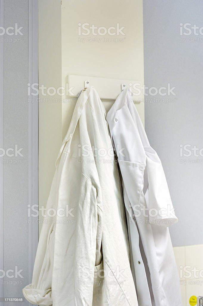 lab coats on hooks stock photo