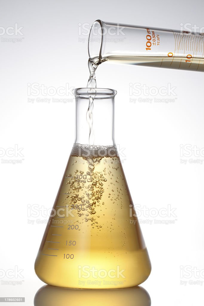 Lab Flask and Pouring Liquid. stock photo