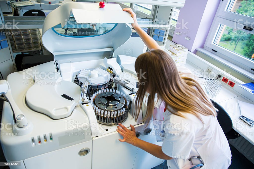 Lab scientist placing test tubes with blood samples in centrifuge stock photo