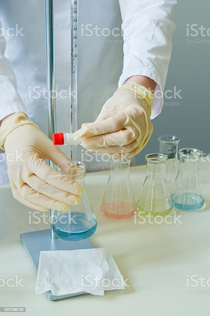 Lab technician work with dilute acids stock photo