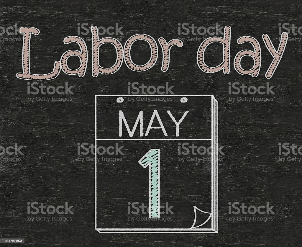 Labor day, with safety helmet on blackboard stock photo