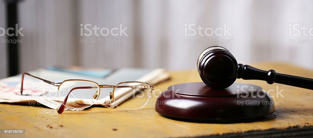 Labor law concept, gavel, glasses and newspaper on wooden table stock photo