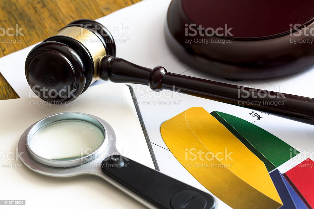 Labor law concept. Gavel, magnifying glass and graphic stock photo