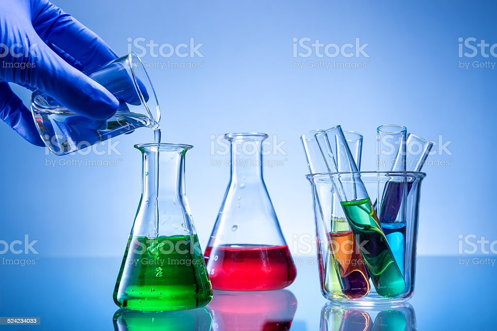 Laboratory equipment, bottles, flasks with color liquid, hand poured stock photo