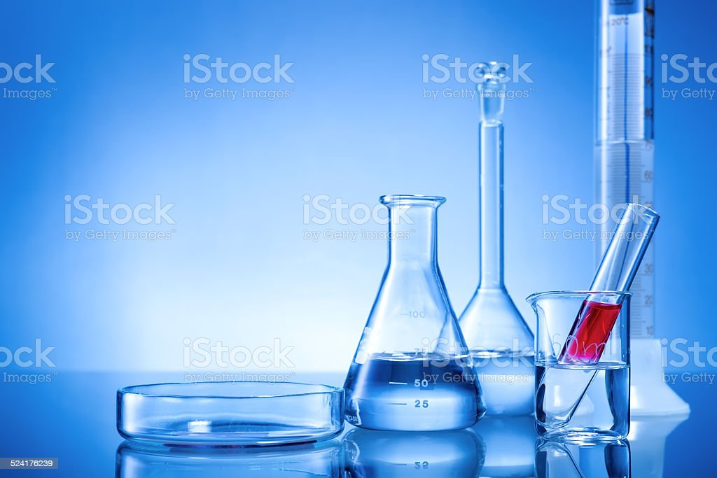 Laboratory equipment, glass flasks, pipettes, red liquid on blue background stock photo