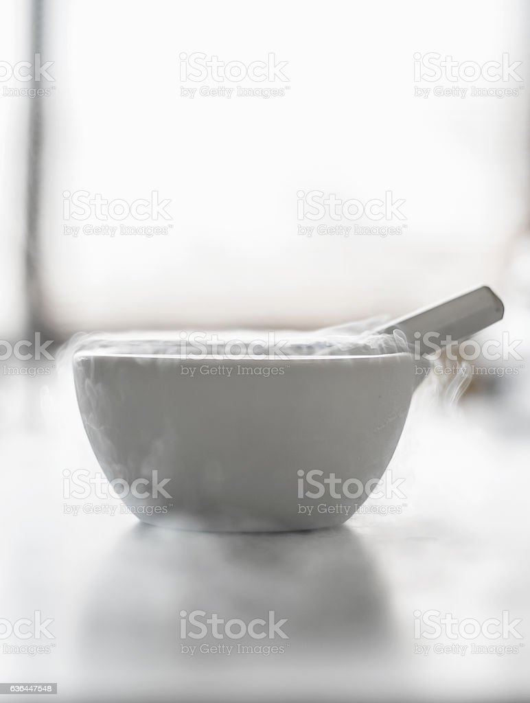 Laboratory experiment with liquid nitrogen in laboratory mortar stock photo