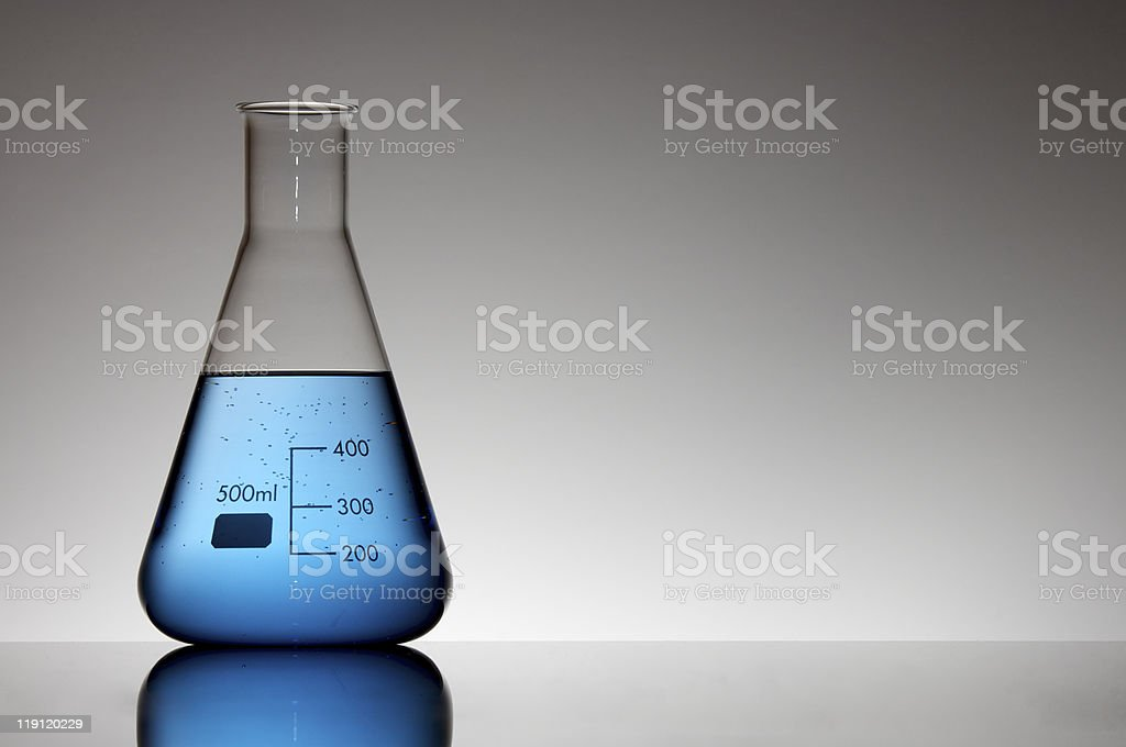A laboratory measurement flask filled with blue liquid royalty-free stock photo