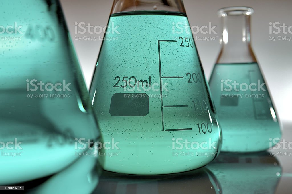 Laboratory measurement tubes with light green liquid inside stock photo