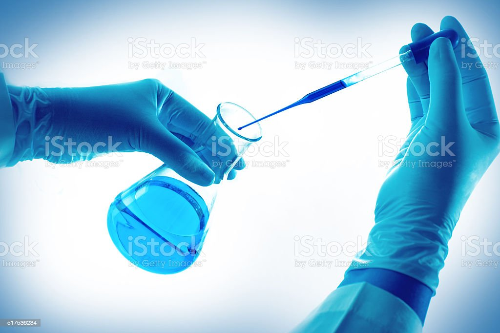 Laboratory research, dropping liquid to test tube stock photo