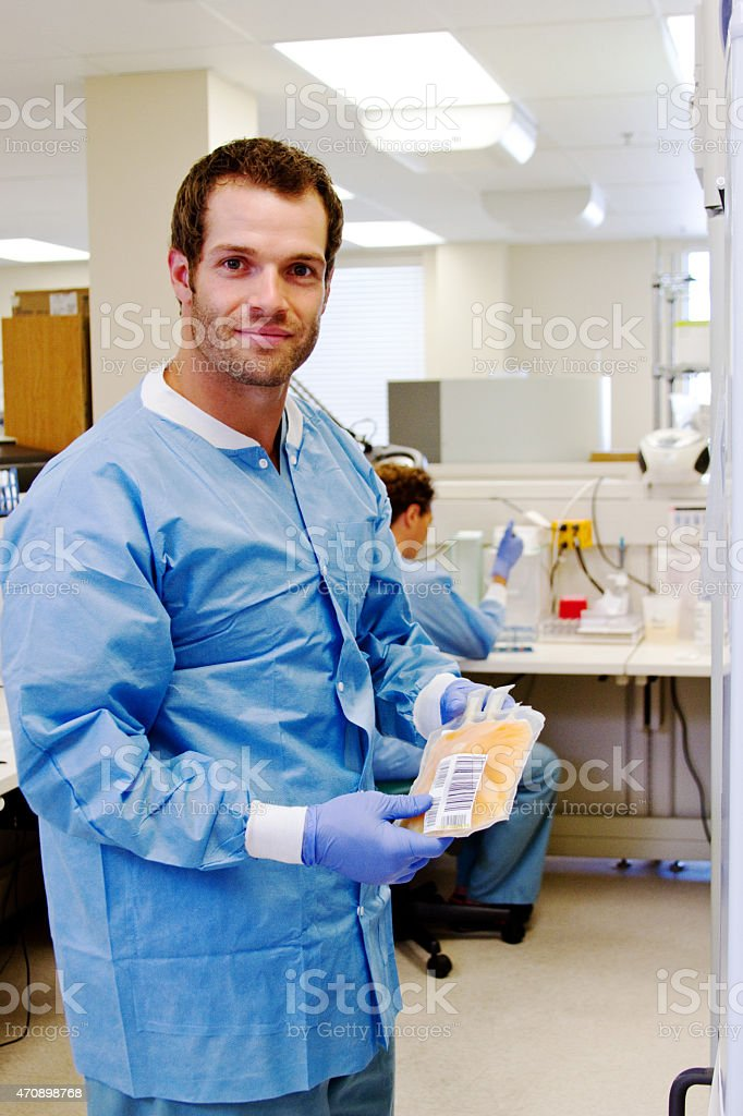 Laboratory technician retrieving plasma from blood bank stock photo