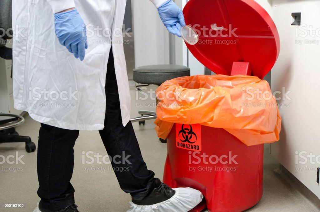 Laboratory worker dropping plastic waste in biohazrd orange trash can stock photo